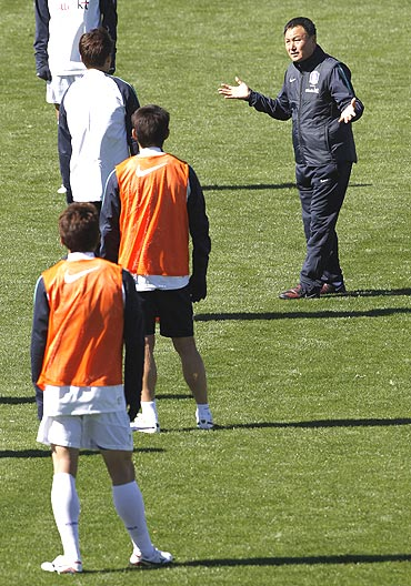 South Korea's coach Huh Jung-moo (right) instructs players during a training session