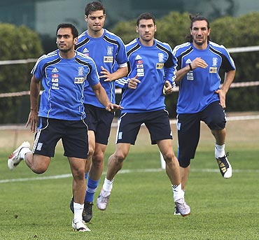 Greeck players stretch during a training session