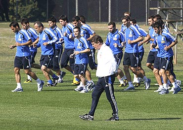 Greece's coach Otto Rehhagel (centre) walks past players during a training session