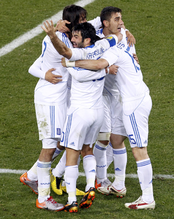 Greece's Giorgos Karagounis celebrates with his teammates after their win