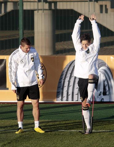 Germany's Mesut Oezil and Lukas Podolski (left) take part in a training session