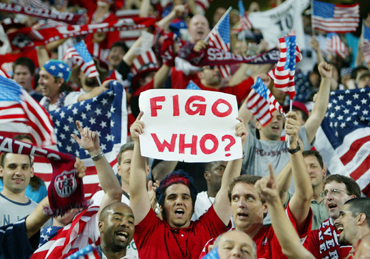 A soccer fan hold a sign in the middle of USA's fans as they celebrate their win against Portugal in their group D World Cup Finals match in Suwon