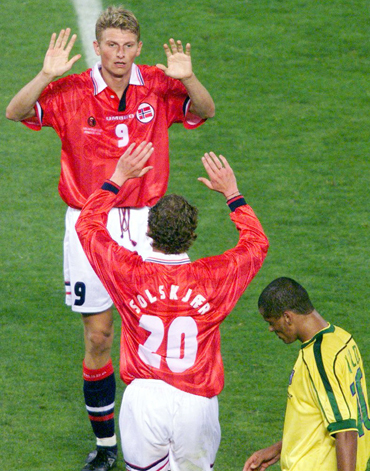 Norway's Tore Andre Flo (top) celebrates with teammate Ole Solskjar after scoring a goal as Brazil's Rivaldo looks on