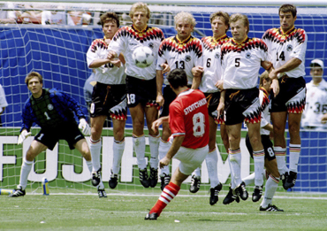Bulgaria's Hristo Stoitchkov (8) kicking the ball past a wall of German defenders and goalkeeper Bodo Illgner (1) to score his team's first goal of their World Cup match at Giants Stadium