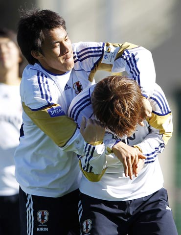 Japan's Okazaki jokes with a team-mate during a training session for the World Cup