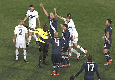 US players argue with referee Koman Coulibaly after a goal scored by teammate Maurice Edu was disallowed