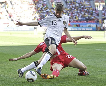 Germany's Thomas Mueller (13) and Serbia's Neven Subotic vie for possession