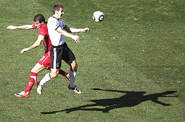 Germany's Miroslav Klose is involved in an aerial duel with Serbia's Dejan Stankovic (left)