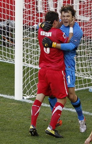 Serbian goalkeeper Vladimir Stojkovic is congratulated after saving a penalty