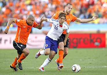 Japan's Yoshito Okubo (centre) is challenged by Netherlands's Nigel de Jong (left) and John Heitinga as they vie for possession