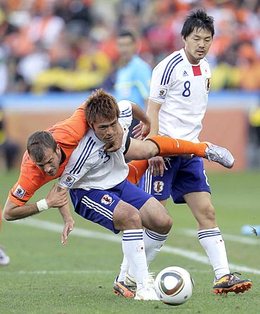 The Netherlands's Rafael van der Vaart (left) and Japan's Yuichi Komano (centre) get into a tangle as they vie for possession