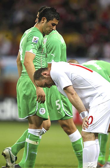 England's Wayne Rooney (right) and Algerian players wear a dejected look after the match