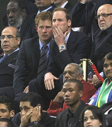 England's Princes William and Harry react during the match