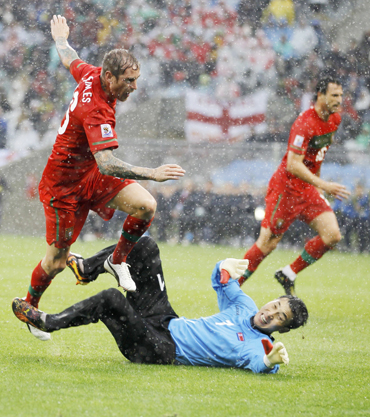 Portugal's Meireles jumps over North Korea's goalkeeper Ri after scoring during a 2010 World Cup Group G soccer match