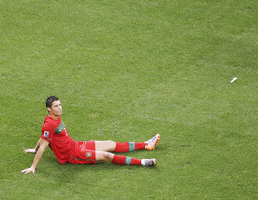 Portugal's Cristiano Ronaldo sits on the ground after the 2010 World Cup Group G soccer match against North Korea