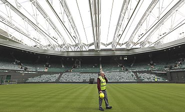 Chief groundsman Eddie Seaward walks underneath the Centre Court retractable roof at the All England Lawn Tennis Club
