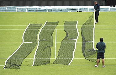 Members of the grounds crew lay nets out on a court in preparation for the Wimbledon Tennis Championships