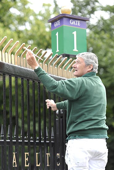 A workman puts the finishing touches to a fence in preparation for the Wimbledon Tennis Championships