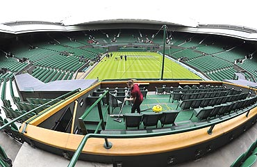 A member of the ground crew vaccums the royal box in preparation for the Wimbledon Tennis Championships