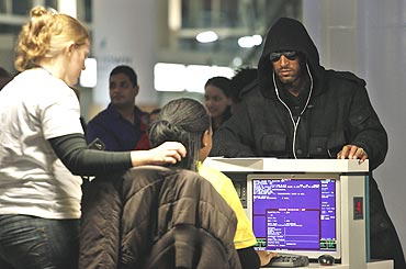 French player Nicolas Anelka (right) waits at the check-in counter as he readies to board a flight to London at the international airport in Cape Town