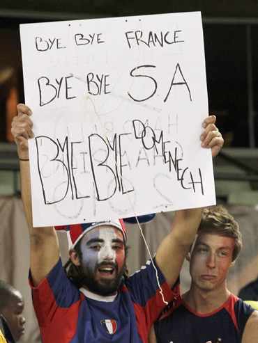 A fan carries a placard bidding farewell to the French and