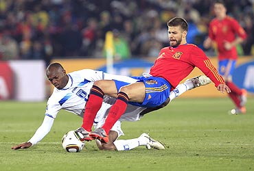Spain's Gerard Pique (right) and with Honduras' David Suazo vie for possession