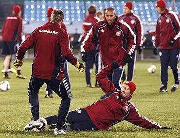 Denmark's Soren Larsen (right) takles teammate Jon Dahl Tomasson (left) during a training session