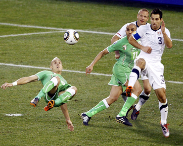 Algeria's Hassan Yebda (L) kicks the ball as United States' Carlos Bocanegra defends during a 2010 World Cup Group C soccer match at Loftus Versfeld stadium in Pretoria