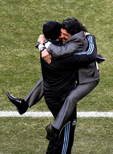 Argentina's coach Diego Maradona (right) celebrates his team's third goal with a member of his coaching staff