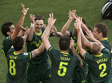 Slovenia's Robert Koren (No. 8) celebrates with team mates after scoring against Algeria
