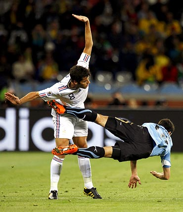 Uruguay's Ignacio Gonzalez (right) falls next to France midfielder Yoann Gourcuff
