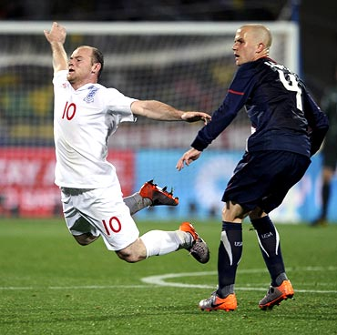 Wayne Rooney (left) falls after clashing with Michael Bradley of the US