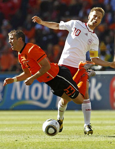 Dutch midfielder Rafael van der Vaart goes to the ground after a tackle by Denmark's Martin Jorgensen