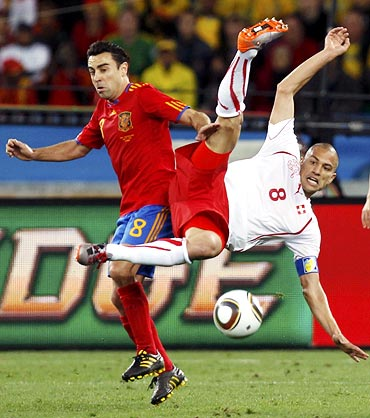 Xavi (left) fights for the ball with Switzerland's Gokhan Inler