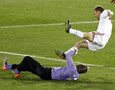 Denmark's Dennis Rommedahl (right) takes a tumble a challenge from Cameroon goalkeeper Hamidou Souleymanou