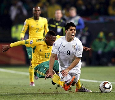 South African Kagisho Dikgacoi (left) and Uruguay's Luis Suarez collide