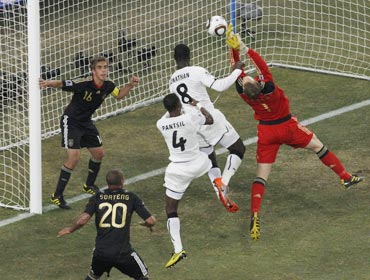 Germany's goalkeeper Neuer makes a save next to Ghana's Mensah