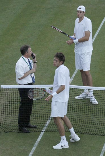 France's Nicolas Mahut and John Isner of the U.S. talk to a tournament official who suspended play due to darkness