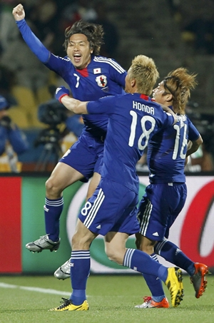Japan's Yasuhito Endo celebrates with team mates Keisuke Honda and Yoshito Okubo after scoring