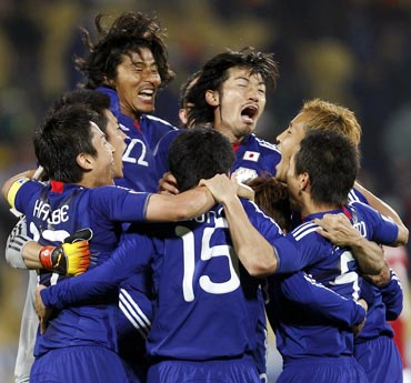 Japan players celebrate after winning their match against Denmark
