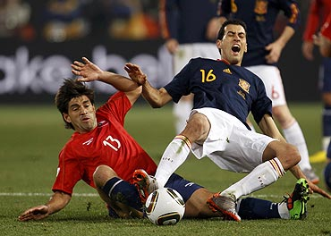 Chile's Marco Estrada (left) challenges Spain's Sergio Busquets during their match