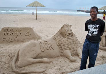 A sand artist shows off his creation