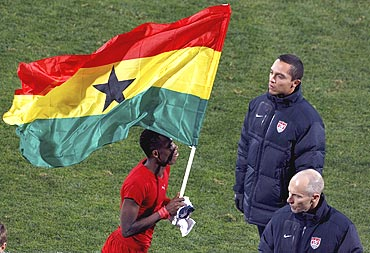 Ghana's John Paintsil runs with the Ghana flag near United States coach Bob Bradley in Rustenburg