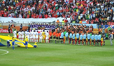 Players stand in respect as the national anthems are played out