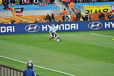 Diego Forlan tries to cuts past a South Korean defender