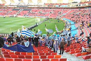 Uruguayan fans cheer and wave their flags