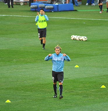 Diego Forlan warms up before the match