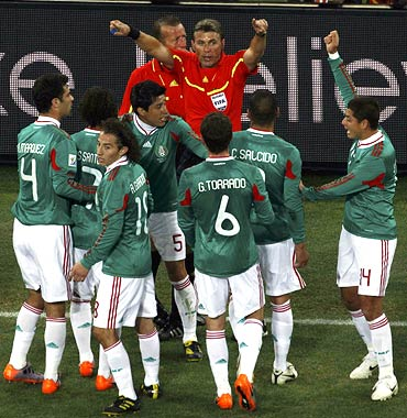 Mexico's players argue with referee Roberto Rosetti of Italy after Carlos Tevez scored the first goal
