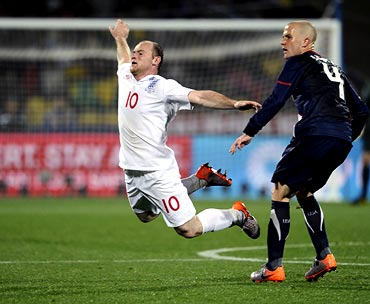 Wayne Rooney is tackled by USA's Michael Bradley