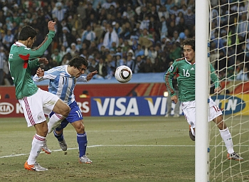 Argentina's  Carlos Tevez scores the first goal against Mexico